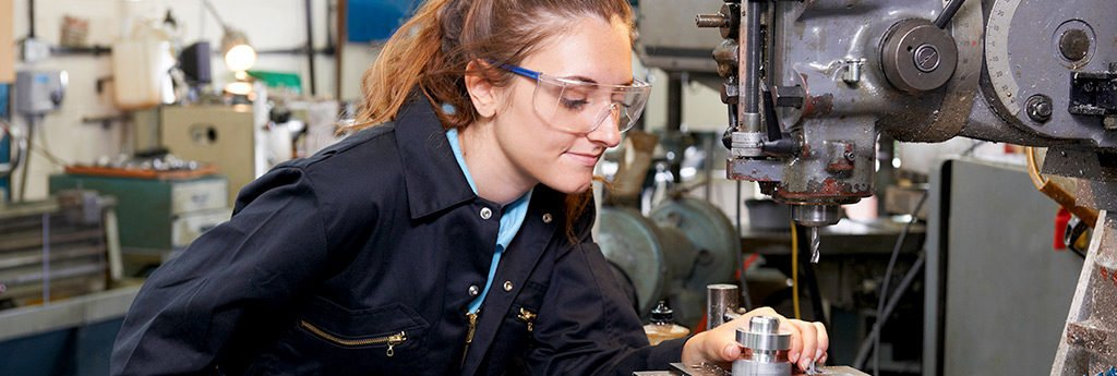 Young woman working in a lab wearing safety glasses